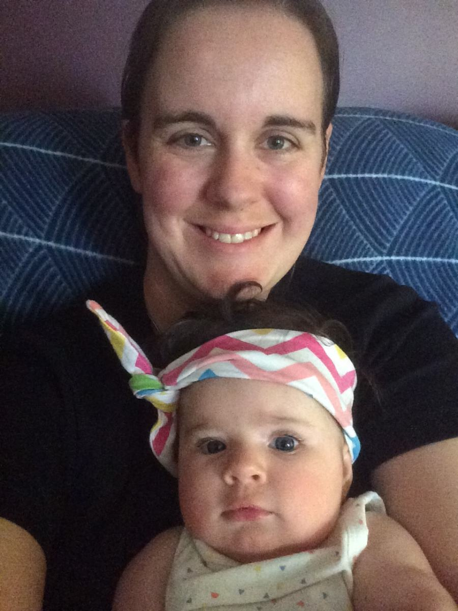 Rachel Angelone with baby on couch postpartum doula melbourne